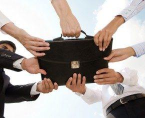Photo of human hands touching a black briefcase
